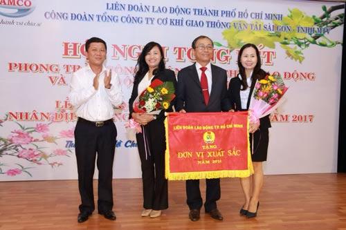 Ông Trần Đoàn Trung (bìa trái), Phó Chủ tịch LĐLĐ TP HCM, trao cờ thi đua xuất sắc cho Công đoàn SAMCO