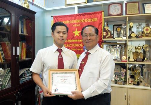 Ông Tạ Long Hỷ (phải), Phó Tổng Giám đốc Vinasun, trao giấy khen và tiền thưởng cho anh Đỗ Trọng Hiếu