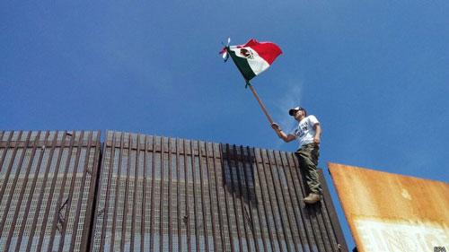 Người biểu tình Mỹ vẫy cờ Mexico tại hàng rào biên giới ngăn cách giữa Mexico và Mỹ ở Tijuana Ảnh: EPA