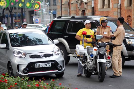 Khi vắng đoàn kiểm tra, tình trạng lấn chiếm vỉa hè, lòng lề đường tái diễn. Trong ảnh: CSGT xử phạt một tài xế ô tô đậu trái phép tại khu vực nhà thờ Đức Bà.
