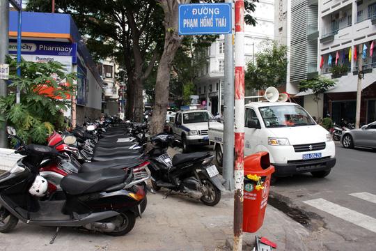 Đây là đường Phạm Hồng Thái (phường Bến Thành, quận 1), xe máy đậu kín vỉa hè, hai ô tô biển xanh thản nhiên chiếm hết lòng lề đường.