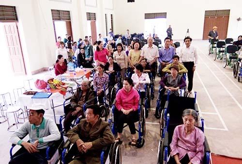 Ông Phan Chánh Dưỡng (áo trắng, đứng giữa) - Giám đốc Quỹ Hỗ trợ Cộng đồng Lawrence S.Ting - trao xe lăn cho người khuyết tật tại Hải Phòng