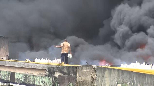 Anh hùng dập lửa trên nóc chợ với chiếc xô trắng - Ảnh 1.