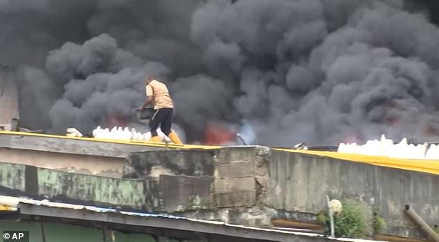 Anh hùng dập lửa trên nóc chợ với chiếc xô trắng - Ảnh 3.