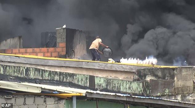 Anh hùng dập lửa trên nóc chợ với chiếc xô trắng - Ảnh 4.