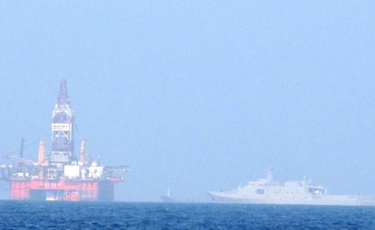 Tàu chiến 2 vạn tấn (bên phải) của Trung Quốc đang kè kè bên cạnh giàn khoan Hải dương 981 hạ đặt trái phép trong vùng biển của Việt Nam vào tháng 5-2014 - Ảnh: HOÀNG DŨNG