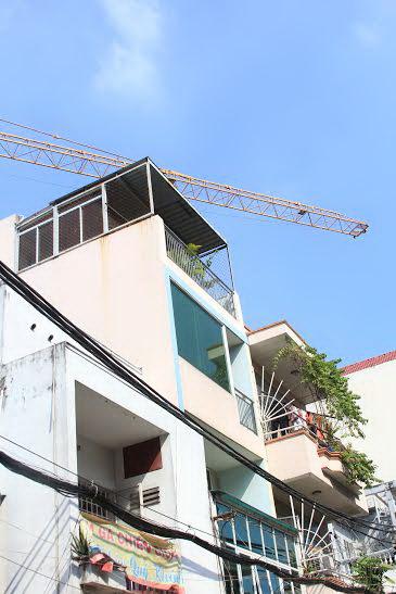 Cần cẩu tháp lơ lửng trên nóc nhà dân ở đường 3 Tháng 2 Ảnh: Sỹ Đông