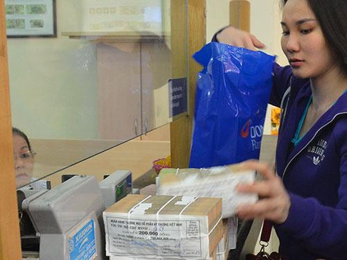 Giao dịch tiền đồng tại Ngân hàng TMCP Đông Á ngày 24-12 Ảnh: TẤN THẠNH