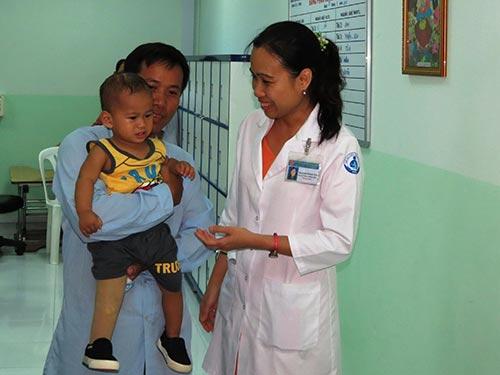 Bé Nguyễn Quốc Huy với chiếc chân giả bên phải mới lắp trong buổi tái khám chiều 29-9