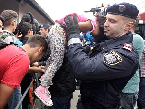 Cảnh sát nhấc bổng một bé gái để không bị thương giữa dòng người tị nạn tại ga đường sắt Nickelsdorf - Áo ngày 5-9 Ảnh: REUTERS