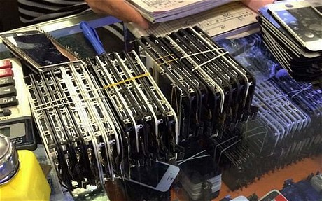 iPhone cũ được tháo gỡ hoàn toàn để kiểm tra từng bộ phận nào còn đang hoạt động. Hoạt động tân trang iPhone diễn ra tại các hộ gia đình ở Thâm Quyến bí mật, người ngoài không được chụp ảnh, quay video. Ảnh chụp tại chợ Hoa Cương Bắc. Nguồn: Telegraph