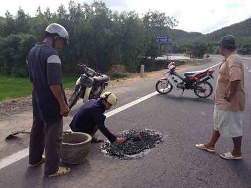 """Vá """"ổ gà"""" theo kiểu thủ công trên Quốc lộ 1 đoạn qua thị xã Sông Cầu, tỉnh Phú Yên Ảnh: HỒNG ÁNH"""