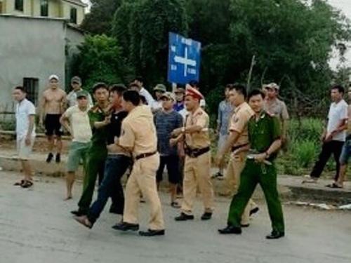 Lực lượng công an khống chế bắt giữ Nguyễn Văn Mười và Đinh Văn Chiến sau khi chém CSGT - Ảnh: Nghĩa Đàn