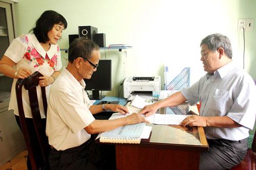 Ông Nguyễn Văn Tính (phải) hướng dẫn thân nhân ngư dân gặp nạn trên biển làm thủ tục xin hỗ trợ