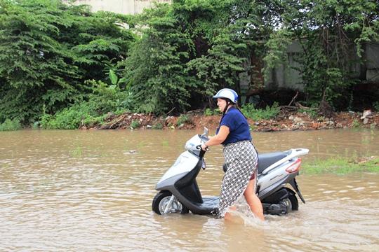 Một người nước ngoài phải bì bõm dắt xe qua đoạn nước ngập trên đường Lương Định Của