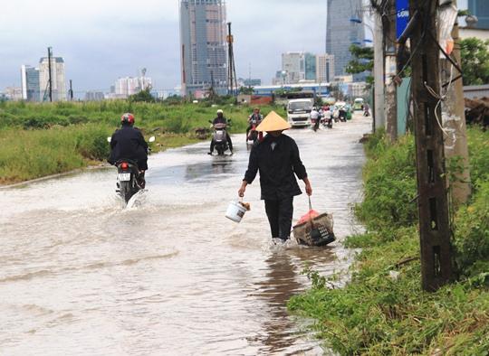 Người dân lội nước trên đường Lương Định Của để bắt cá