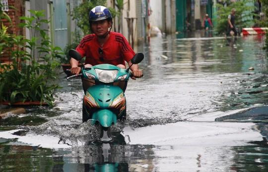 Nước ngập gần đến yên xe máy trên đường Ấp Chiến Lược (quận Bình Tân) sáng 16-9