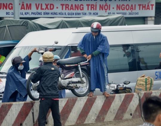 Do kẹt xe, nhiều người phải nâng xe máy qua dải phân cách để lưu thông ngược chiều bất chấp lệnh cấm
