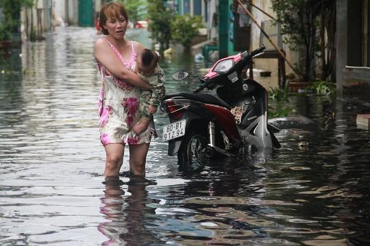 Người phụ nữ bế con lội bì bõm trong dòng nước đen trên đường Ấp Chiến Lược (quận Bình Tân) sáng 16-9