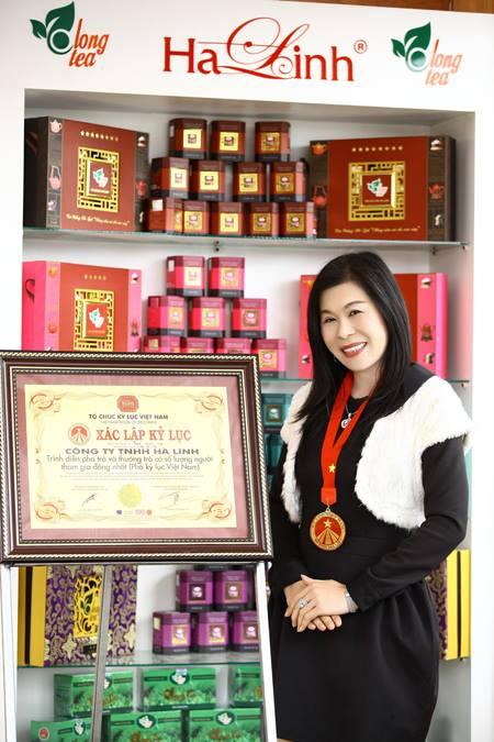 Bà Hà Linh bên bằng xác nhận kỷ lục số lượng người uống trà lớn nhất Việt Nam do tổ chức kỷ lục Việt Nam trao tặng.