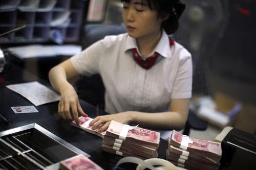Nữ giao dịch viên đếm tiền tại Khu vực Tự do Thương mại Thượng Hải - Trung Quốc Ảnh: REUTERS