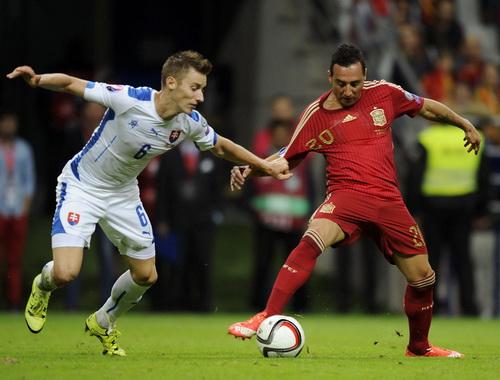 Santi Cazorla (phải) tranh bóng với hậu vệ Slovakia