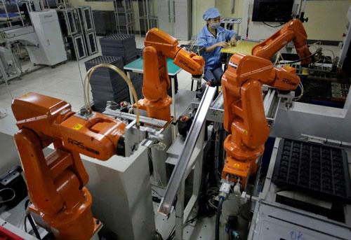 Công nhân làm việc bên cạnh cánh tay robot tại Nhà máy Rapoo Technology ở TP Thâm Quyến - Trung Quốc Ảnh: AP