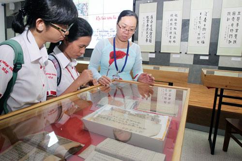 Nhân viên Thư viện Khoa học Tổng hợp TP HCM hướng dẫn tham quan triển lãm cho sinh viên trong ngày khai mạc Ảnh: Hoàng Triều