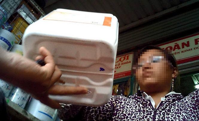 Chủ một sạp kinh doanh hóa chất, hương liệu ở chợ Kim Biên (Q.5, TP HCM) giới thiệu tinh chất pha cà phê cho khách - Ảnh: H.L.