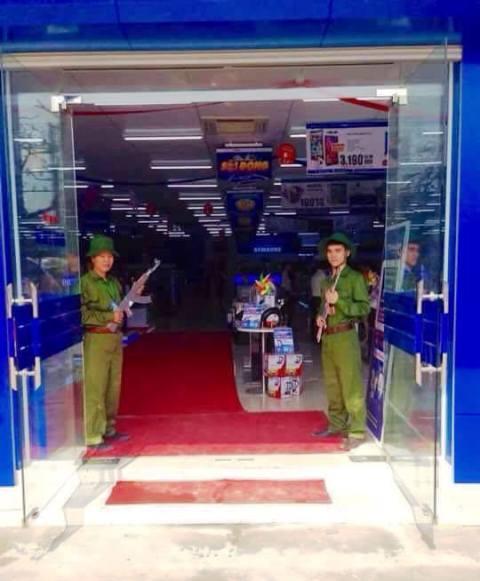 Hình ảnh đôi nam nữ mặc quân phục xanh, cầm súng đứng trước siêu thị được cho là chụp tại siêu thị điện máy Trần Anh (Nam Định) - Ảnh facebook