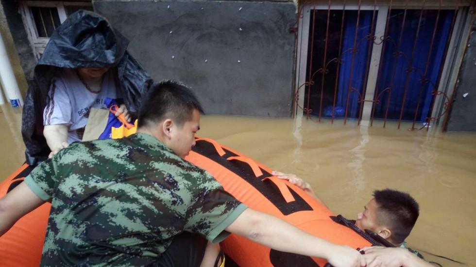 Một người đàn ông trèo lên xuồng cứu hộ ở Giang Tây. Ành: TÂN HOA XÃ
