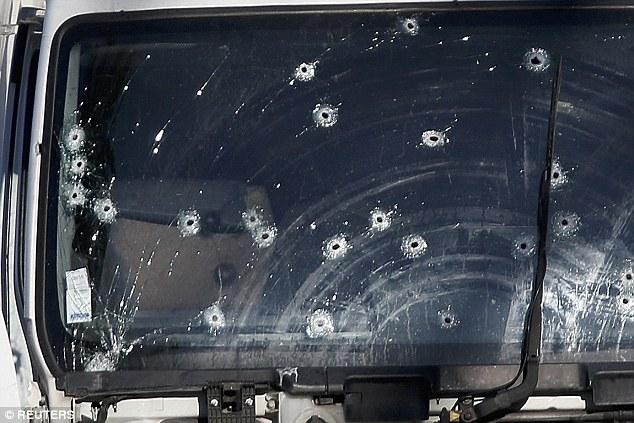 Kính xe tải lỗ chỗ đạn... Ảnh: Reuters