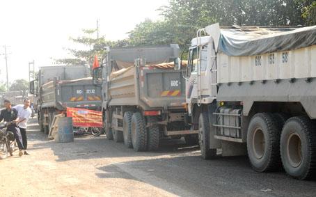 Dòng xe tải ben bị người dân chặn lại, xếp hàng dài. Ảnh: T.HẢI