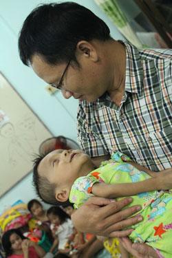 Tác giả với bé Hoài Thương - một ca xương thủy tinh nặng nhất ở trung tâm Ảnh: SỸ PHONG