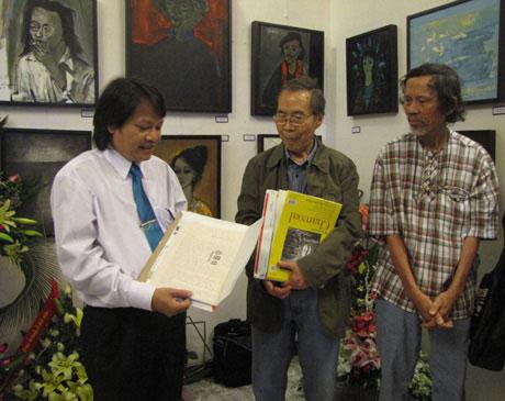 Tại phòng tranh Gác Trịnh (Huế), họa sĩ Đinh Cường (giữa) trao kỷ vật quý về nhạc sĩ Trịnh Công Sơn cho tác giả bài viết - Hồ Đăng Thanh Ngọc (bìa trái). Bìa phải là họa sĩ Phan Ngọc Minh. (Ảnh do tác giả cung cấp)