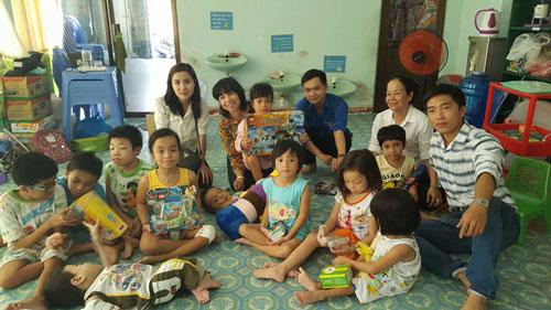 Chị Hồng Lê (ngồi giữa) tặng quà cho các cháu mắc bệnh xương thủy tinh Ảnh: SỸ PHONG