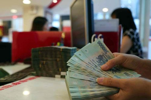 Lãi suất huy động VNĐ đang hấp dẫn hơn so với USD khiến nhiều ngân hàng lách quy định để giữ ổn định nguồn gửi ngoại tệ. Ảnh: HOÀNG TRIỀU