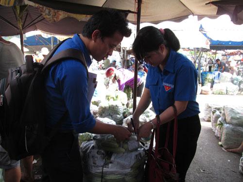 Lực lượng chức năng lấy mẫu rau quả tại chợ đầu mối Hóc Môn