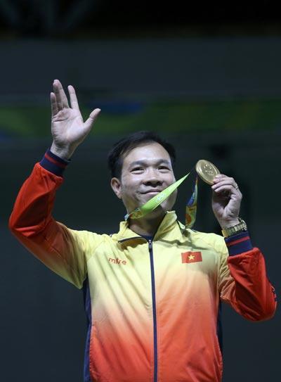 Xạ thủ Hoàng Xuân Vinh với chiếc HCV Olympic lịch sử của thể thao Việt Nam Ảnh: REUTERS