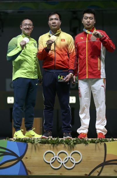 VĐV Hoàng Xuân Vinh trên bục nhận huy chương rạng sáng 7-8 Ảnh: REUTERS