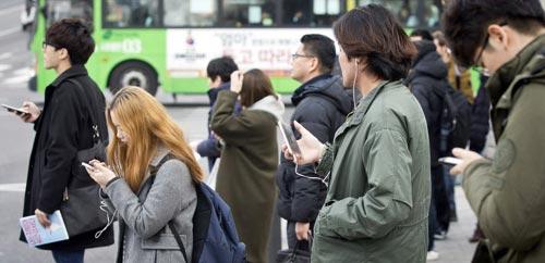 Nhiều người mải mê dùng smartphone ngoài đường phố ở thủ đô Seoul - Hàn Quốc Ảnh: CHOSUN ILBO