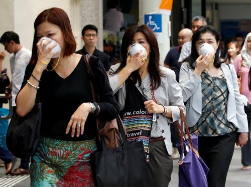 Nhiều người dân Singapore phải đeo khẩu trang khi ra đường hôm 26-8 do khói mù Ảnh: REUTERS