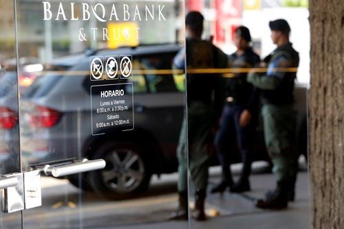 Cảnh sát đứng bên ngoài trụ sở Ngân hàng Balboa ở TP Panama City sau vụ doanh nhân Nidal Waked bị bắt vì nghi điều hành mạng lưới rửa tiền cho tội phạm ma túy Ảnh: REUTERS