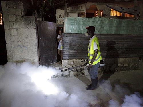 Nhân viên y tế phun thuốc diệt muỗi để ngăn chặn virus Zika tại thủ đô Port-au-Prince của Haiti hôm 2-2 Ảnh: REUTERS