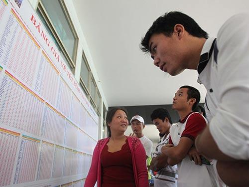Hành khách xem bảng giá vé Tết Bính Thân ở ga Sài Gòn Ảnh: HOÀNG TRIỀU