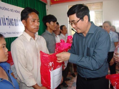 Bộ trưởng Cao Đức Phát tặng quà cho ngư dân ở cảng cá Thuận An Ảnh: Quang Nhật