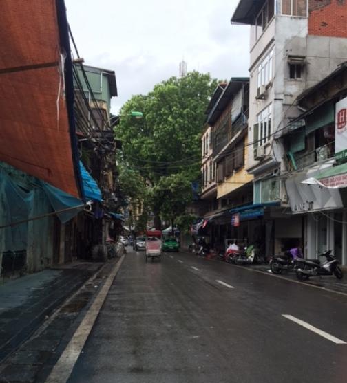 Phố Lương Văn Can hàng ngày bày bán đồ chơi trẻ em tràn ngập vỉa hè. Hôm nay mưa bão, vỉa hè trở nên rộng rãi và trơ ra những giá đỡ thường ngày vẫn treo đồ chơi