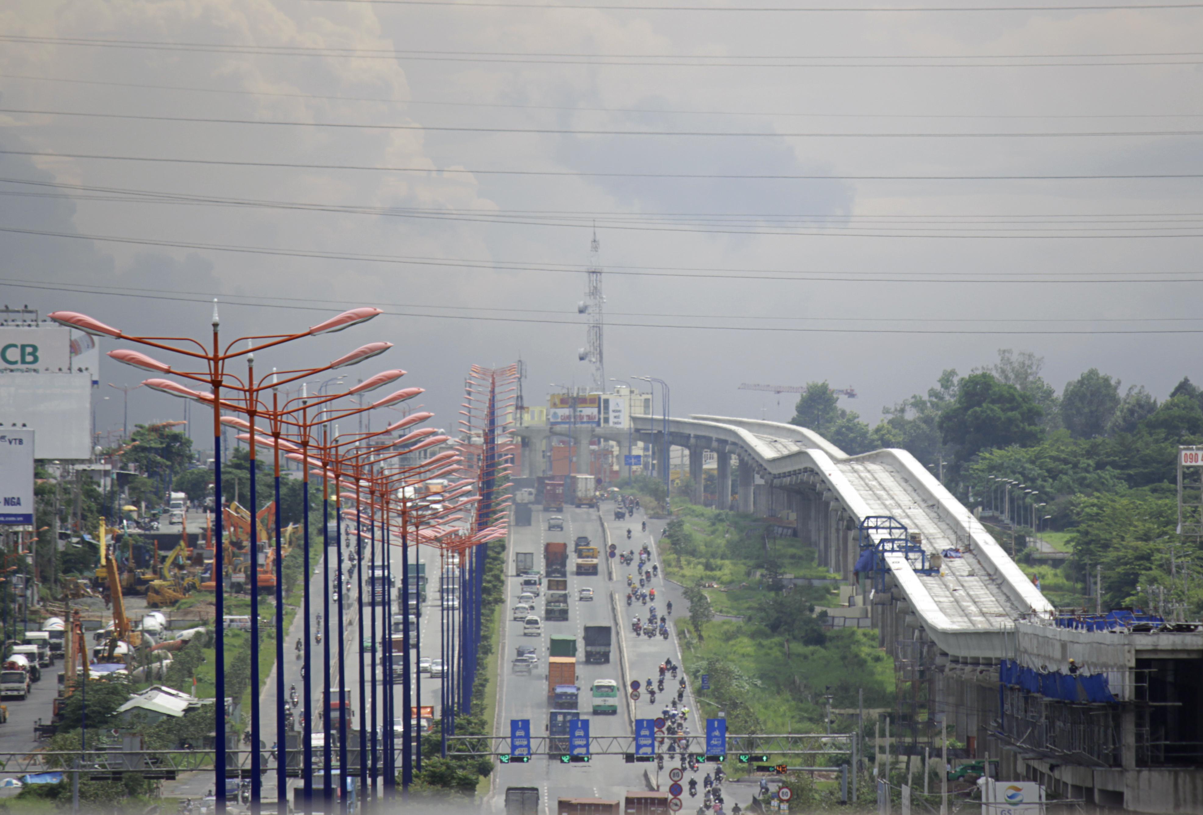 Hình ảnh tuyến metro nhấp nhô mềm mại như cơn sóng trên đoạn xa lộ Hà Nội đoạn ngã tư Thủ Đức. Dự án Metro Bến Thành - Suối Tiên được khởi công vào tháng 8/2012. Theo thiết kế, tuyến Metro đi qua các quận 1, 2, 9, Bình Thạnh, Thủ Đức (TP HCM) và huyện Dĩ An (Bình Dương).