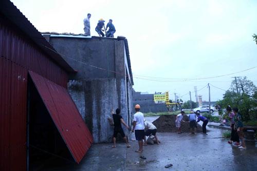Người dân đặt bao cát chống gió bão làm tốc mái (xã Hải Thanh, huyện Hải Hậu, tỉnh Nam Định) Ảnh: MINH QUYẾT