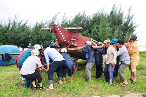 Hai tàu cá của ngư dân tỉnh Quảng Ngãi bị chìm ở cửa biển Cửa Đại (ảnh trên) và di dời các thuyền vào bờ tránh bão tại tỉnh Quảng NamẢnh: TỬ TRỰC-TRẦN THƯỜNG